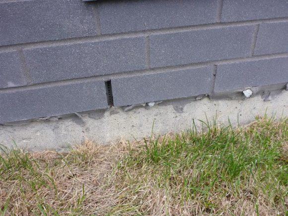 Chantepleure à la base du parement en briques